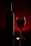 Wine bottle and glass over dark red Stock Image