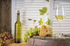 Wine bottle, glass of white wine with cheese and grape. Still life of white wine with wooden keg. Wine bottle, glass of white wine with cheese and grape on a Stock Image