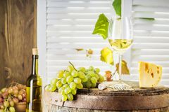 Wine bottle, glass of white wine with cheese and grape. Still life of white wine with wooden keg. Wine bottle, glass of white wine with cheese and grape on a Royalty Free Stock Images