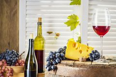 Wine bottle, glass of white wine with cheese and grape. Still life of red wine with wooden keg. Wine bottle, glass of red wine with cheese and grape on a old Royalty Free Stock Photo