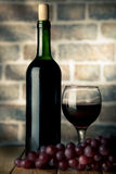 Wine bottle and glass on a wooden table with bricks wall backgro Royalty Free Stock Photos