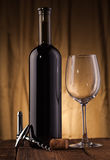 Wine bottle with glass on wooden table Royalty Free Stock Photo