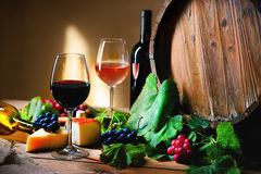 Wine bottle, glasses, cheese, grapes and barrel. On a table Royalty Free Stock Photos