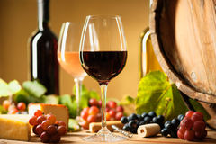 Wine bottle, glasses, cheese, grapes and barrel. On a table Royalty Free Stock Photo