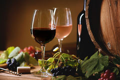 Wine bottle, glasses, grapes and barrel. On a table Stock Image