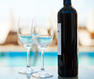 Wine bottle and glasses near sea water Stock Photos