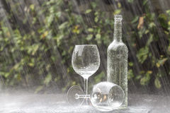 Wine Bottle and Glasses in Summer rain. A winebottle and two glasses on a garden table during heavy summer rain Royalty Free Stock Photos