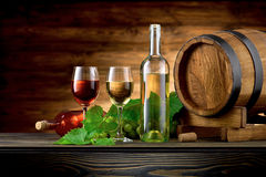 Wine bottle and glasses with wooden barrel. On the table stock photos