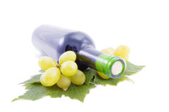 Wine Bottle and grapes with leaves. Royalty Free Stock Photos