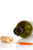 Wine bottle on its side with cork. Red wine bottle on its side with wine spilling out with cork Stock Photo