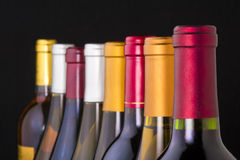Wine bottle necks. Colorful wine bottle necks shot on black with limited depth of field royalty free stock photos