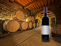 Wine bottle with oak wine barrels Stock Photos