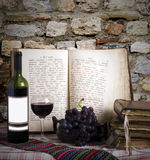 Wine bottle and old books. Against rocky wall Stock Image