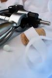 Wine bottle opener against waiter's uniform. Cork has apron ribbon draped over it stock image