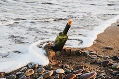 Wine bottle on a sandy beach. Wine bottle with a cork stopper on a sandy beach by the sea stock photo