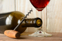 Wine Bottle Still Life with Cork Screw. Wine still life with a bottle on its side and the bottom of a glass of red wine and a cork screw leaning on the bottle Stock Photo
