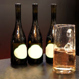 Wine bottle. Three bottles of rose wine and a glass of wine Royalty Free Stock Photos