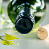 Wine bottle with vine and wine cork put on the board.Close up wi. Close up wine Bottle with grape vine and wine cork on white table. Shallow depth of field Royalty Free Stock Images