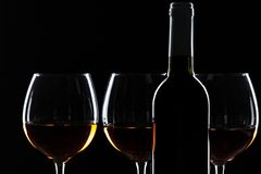 Wine bottle and wine glass in a black background royalty free stock photos