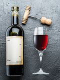 Wine bottle, wine glass and corkscrew on the graphite board. Stock Image