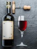 Wine bottle, wine glass and corkscrew on the graphite board. Stock Photo