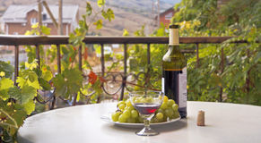 Wine bottle,wine glass and grapes on a round table. Balcony,wreathed with grape leaves. Royalty Free Stock Image