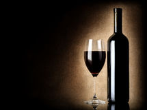 Wine bottle and wineglass on a old background. Wine bottle and wineglass on a background of old canvas Stock Image