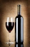 Wine bottle and wineglass on a old canvas Stock Photos