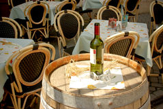 Wine bottle and wineglasses on barrel in street ca Stock Photos