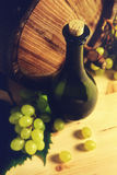 Wine bottle, wooden barrel and white grapes. Stock Image