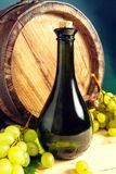 Wine bottle, wooden barrel and white grapes. Stock Photography