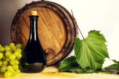 Wine bottle, wooden barrel and white grapes. Stock Photos
