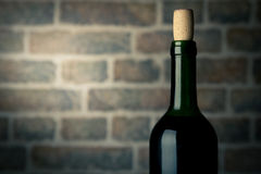 Wine bottle on a wooden table with bricks wall background close Stock Photos