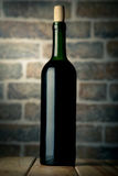 Wine bottle on a wooden table with bricks wall background Stock Photo