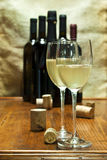 Wine bottles. Two glasses of white and sparkling wine with some corks and bottles on the background Royalty Free Stock Image