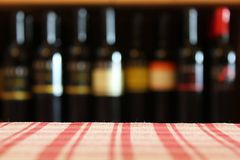 Wine bottles. On a shelf in the foreground tablecloth shot with limited depth of field stock images