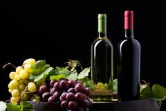 Wine bottles on a barrel. With wine accessories royalty free stock photography
