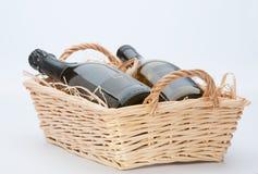 Wine Bottles In Basket. Two wine bottles in a raffia lined wicker basket Royalty Free Stock Photo