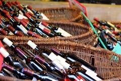 Wine bottles in baskets. French market scene : wine bottles in baskets. Side view Stock Image