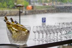 Wine bottles in bowl with ice cubes, many glasses on a rainy window background. Wine bottles in bowl with ice cubes and many glasses on a rainy window background royalty free stock image