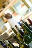 Wine bottles with cook in background Royalty Free Stock Image