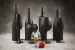 4 wine bottles with corresponding stemware. 4 Bottles and Flutes painted in flat black on a mottled grey background arranged around a brandy snifter and royalty free stock photography