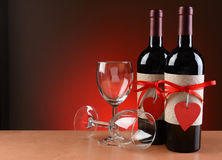 Wine Bottles Decorated For Valentines Day. Closeup of a wine bottles decorated for Valentines Day. Two empty wineglasses are next to the bottles with one on its Stock Images