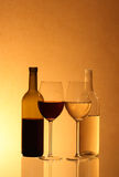 Wine bottles and glasses. Details of two bottles of wine and wine glasses or goblets on a glowing background royalty free stock images