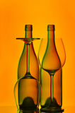 Wine bottles and glasses. Silhouetted bottles of wine and glasses with dim background Stock Images
