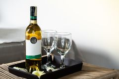 Wine bottles and glasses of wine on tray. royalty free stock photos