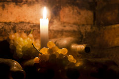 Wine bottles and grapes with candle. Backlited grapes with wine bottles Stock Images