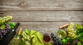 Wine bottles with grapes and corks on wooden background Royalty Free Stock Image