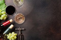 Wine bottles and grapes. On stone table. Top view with space for your text Stock Photo
