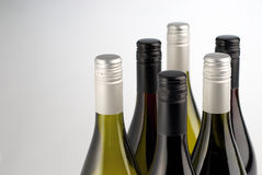 Wine bottles isolated on white. Close up of top half of red and white white wine bottles, isolated on white background Royalty Free Stock Image